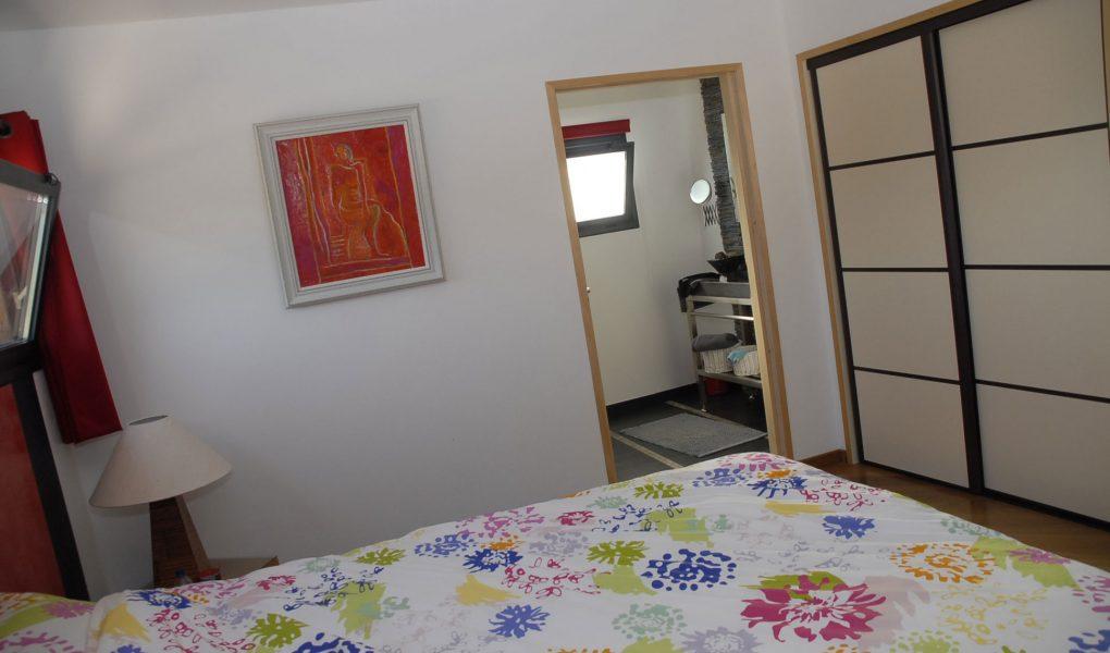 Photo du lit et de la porte vers la salle de bain