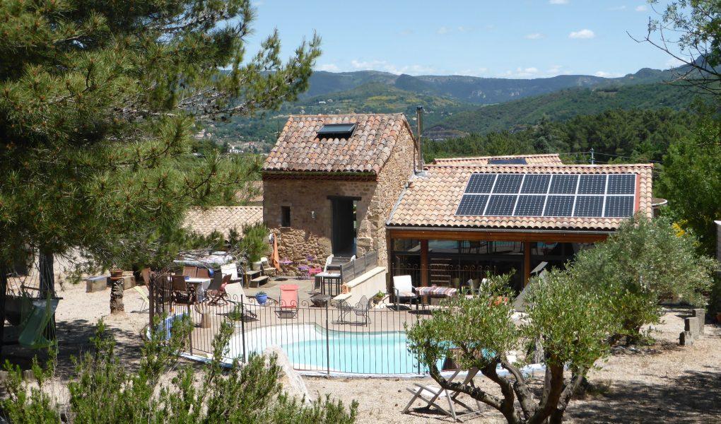 Une vue extérieure de la chambre d'hôte, avec la piscine et des panneaux solaires sur le toit